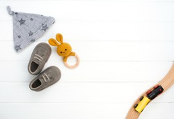 Baby hat, booties and wooden teether and train toy on white wooden background with blank space for text. Top view, flat lay.