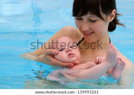 baby having swimming lesson with mother