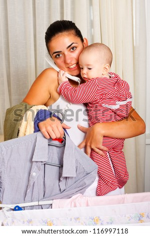 Baby helping her mother to talk on the phone while she is doing the laundry.