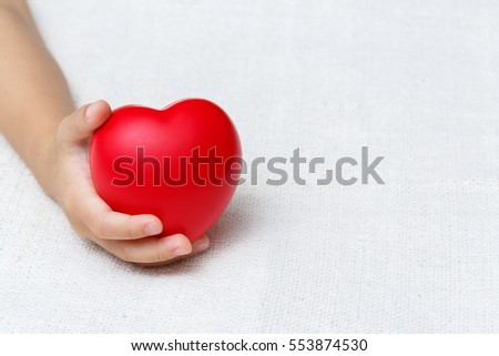 Baby hold red color heart in palm hands, love and health concept #553874530