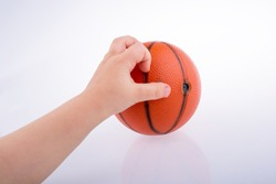 Baby holding an orange basketball model on a white background