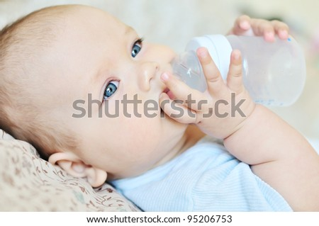 baby holding bottle and drinking water