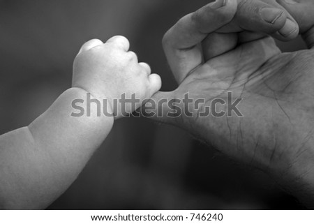 baby holding fathers hand