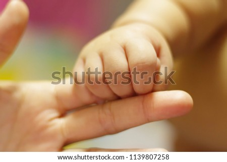Baby holding finger of his mother giving senses of attachment and bonding. The image taken with a selective focus stressing an emotional scene.