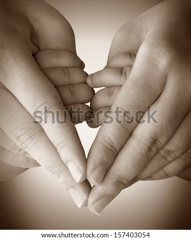 Baby holding mother finger and together form a heart shape