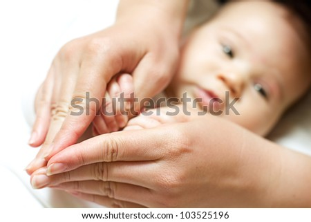 Baby holding mother finger and together form a heart shape by hand.