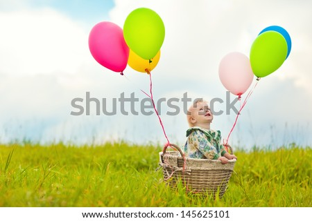 Baby in a basket with balloons