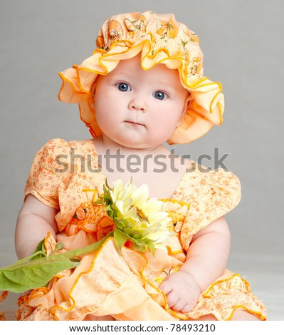 baby in a beautiful dress with a sunflower