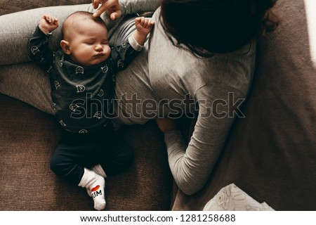 Baby in a deep sleep in the lap of his mother at home. Mother sitting on couch with her baby sleeping in her lap and touching his head.