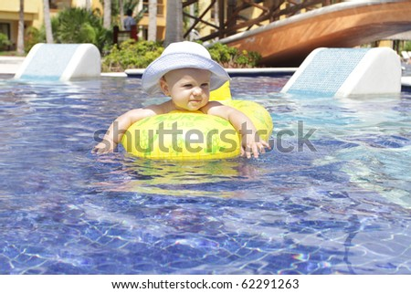 Baby in a floating in a tropical resort pool