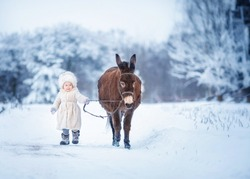 Baby in a fur hat with a donkey. Image with selective focus and toning.