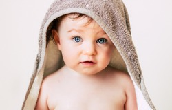 Baby in a hooded towel after shower or bath isolated on white. Hygiene, textile, baby wash, toddler concept