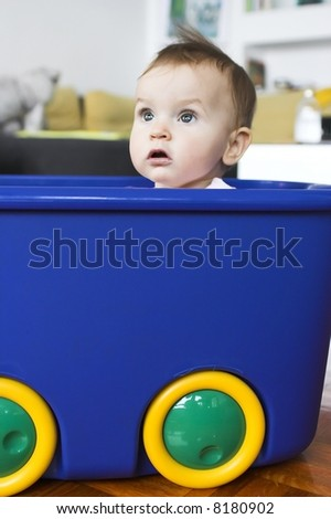 Baby in a plastic tray playing- pretending to drive a car - stock photo