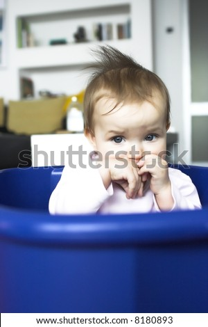 Baby in a plastic tray - sad face expression