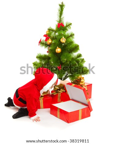 Baby in a red santa costume opening a present box