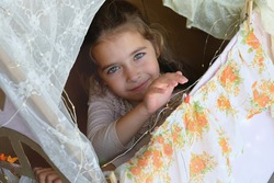 Baby in a toy house. Child plays in a cardboard box. Theatrical scenery for the little princess. Big green eyes baby. Beautiful mysterious face. Kid playing with curtains. Little girl dreamer. Happy