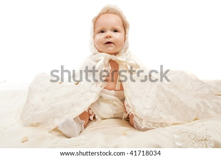 Baby in baptismal clothing sitting on the satin blanket