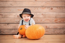baby in black hat with pumpkins on wooden background