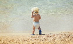 Baby in diapers and hat on the beach - summer joy