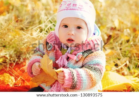 baby in fall time sitting under with leaf