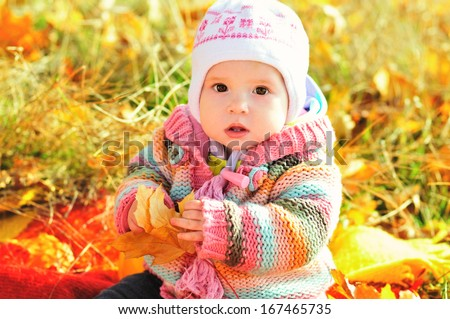 baby in fall time sitting with leaf