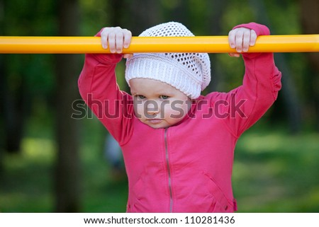 Baby in hat playing on the playground