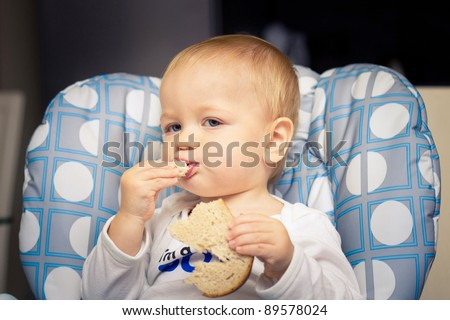 Baby in high chair eating bread