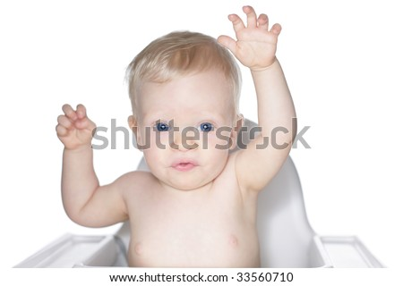 Baby in high chair reaching out with both arms.