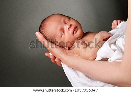 baby in mother's arms and wrapped up in white blanket just been cared for after having a good sleep in bed stock photograph stock photo