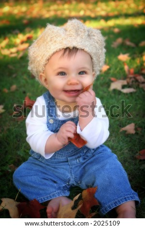 baby in overalls and crocheted hat with leaves