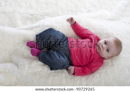 baby in pink lying on a beige carpet