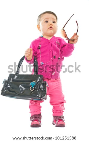 Baby in pink with sunglasses and hand bag isolated on white