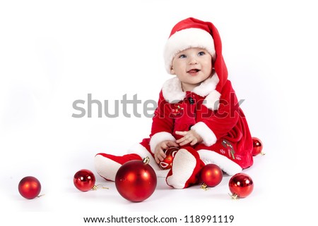 Baby in red costume playing with Christmas decoration
