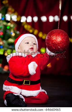 Baby in Santa costume playing with huge Christmas ball
