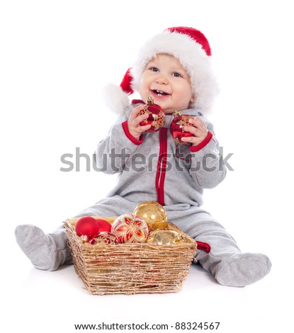 Baby in Santa hat playing with Christmas balls isolated on white background