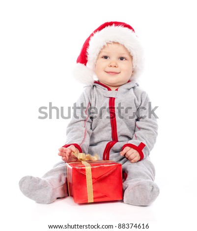 Baby in Santa hat playing with Christmas gift box isolated on white background