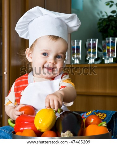 Baby in the cook costume in the white hat with vegetables