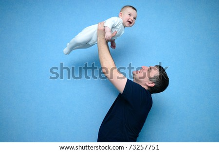 Baby in the daddy hands. Blue background.