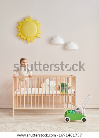 Baby in the wooden cradle and crib style, modern room and toy in the pink wall. Foto stock ©