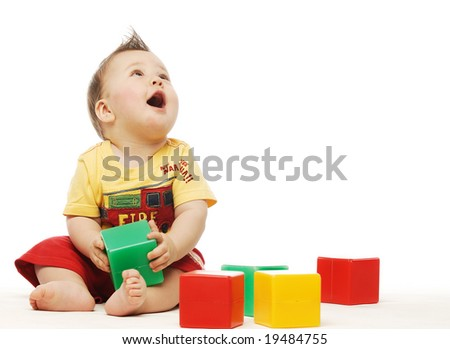 Baby in yellow shirt playing with bright blocks looking up in surprise