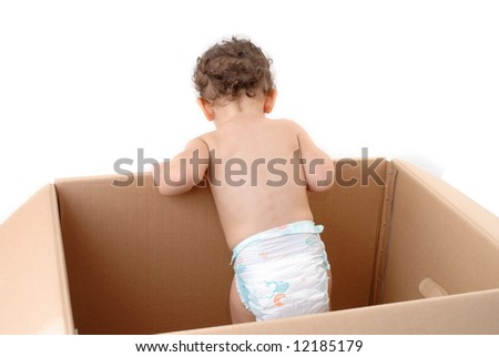 Baby inside of cardboard box looking outside.