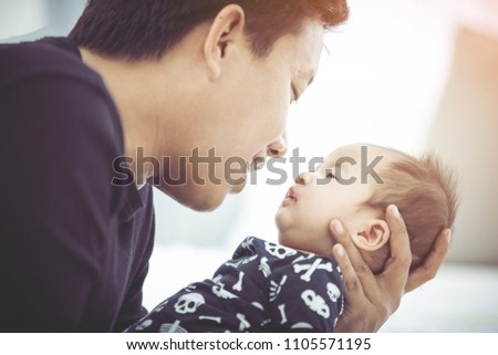 baby is being carried by father. father always carries him because he loves his son #1105571195