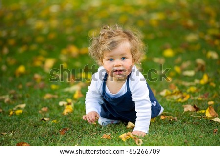 baby is crawling in the fall-meadow