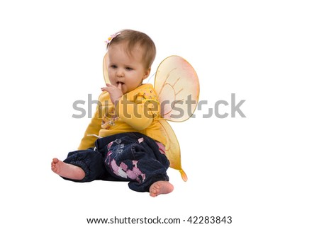 Baby is creeping on the floor. Photo of small child is wearing in yellow jersey and wings. Baby is 9 months.