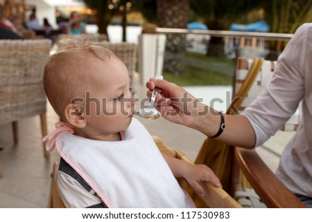 Baby is eating soup from mother's hand in the restaurant