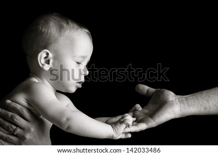 Baby is holding father's hand. Black and white photo.