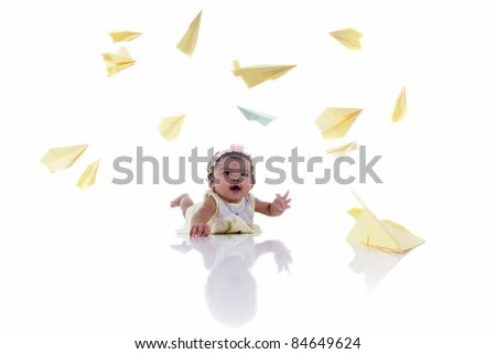 Baby is playing with paper planes