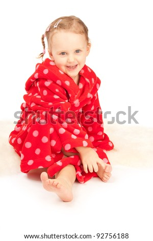 Baby is sitting on the floor in red dressing-gown
