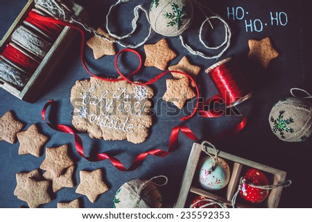 Baby it\'s cold outside gingerbread cookies with ribbons and vintage ornaments on a black background