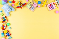 Baby kids toy frame with educational, developmental, musical, learning toys on pastel yellow background. Top view